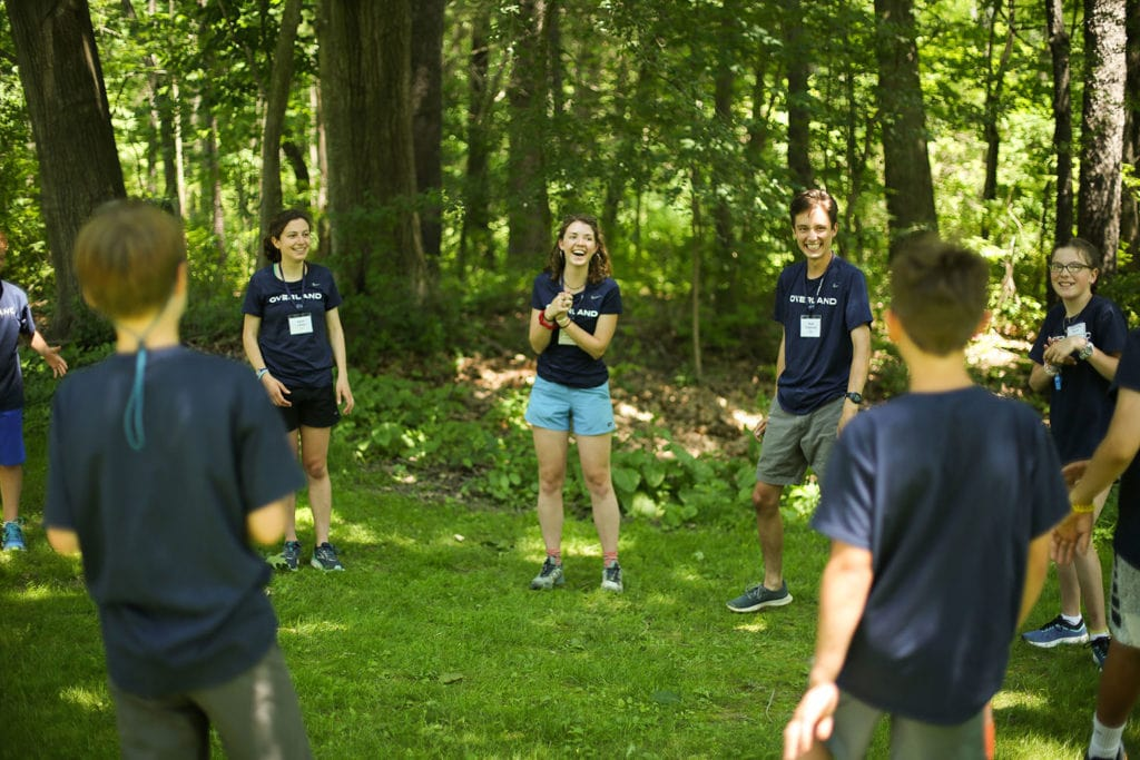A group of kids and leaders playing a game to get ot know one another of the first day of a summer trip.