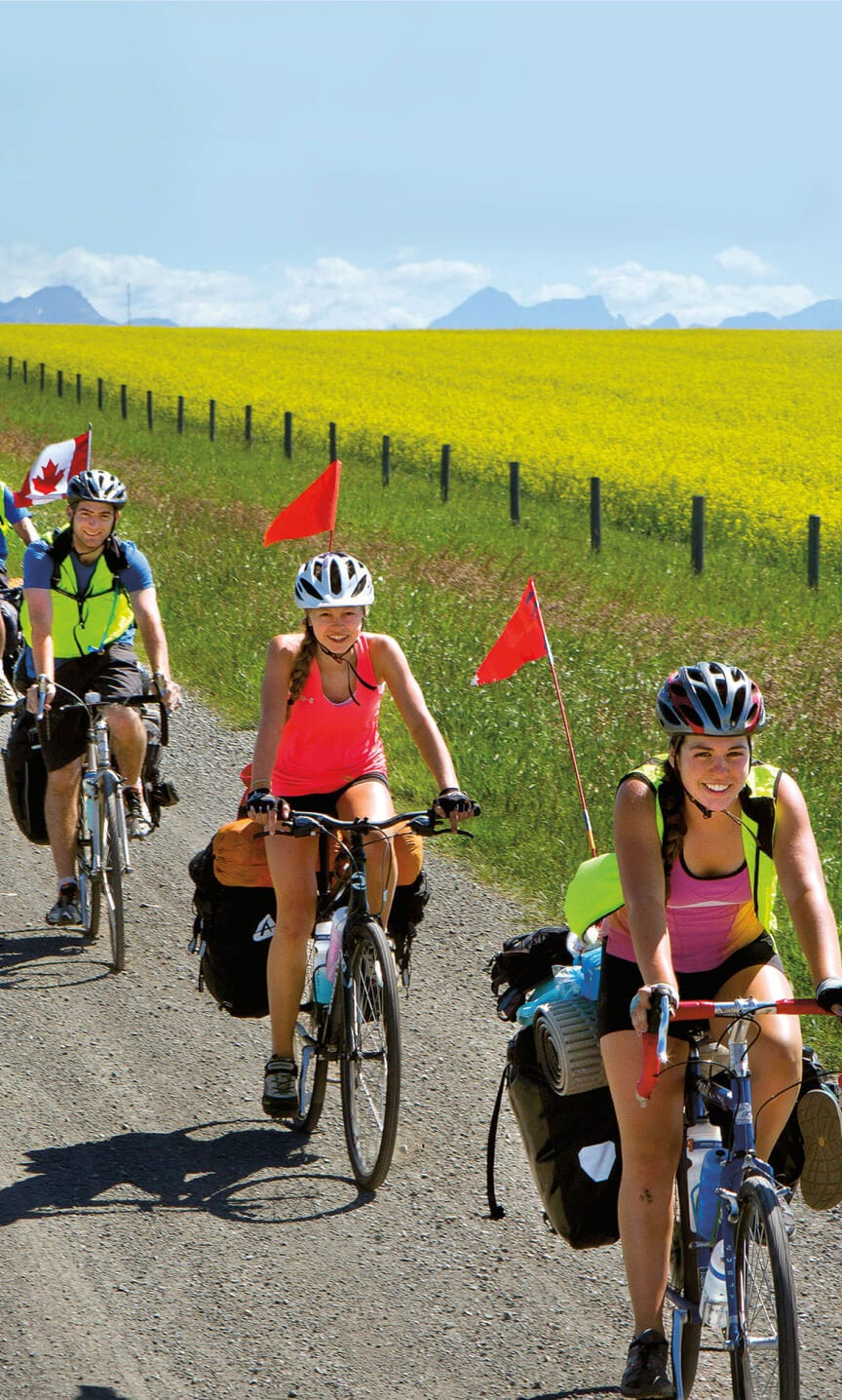 Teens biking through open meadows with summer wildflowers while on an adventure trip