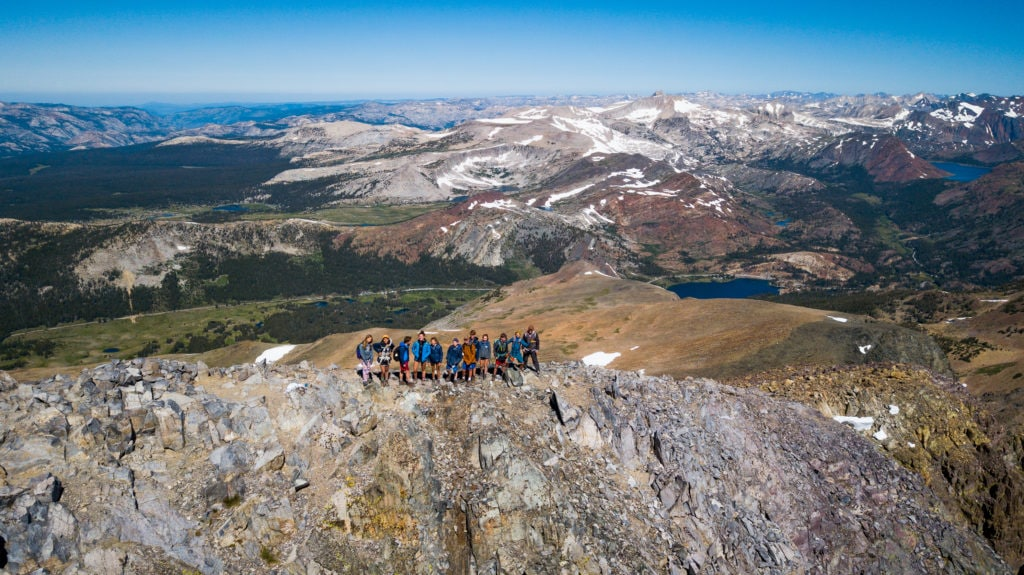 A hiking group poses on a ridge in the Sierra Mountains during their most challenging hike of the summer.