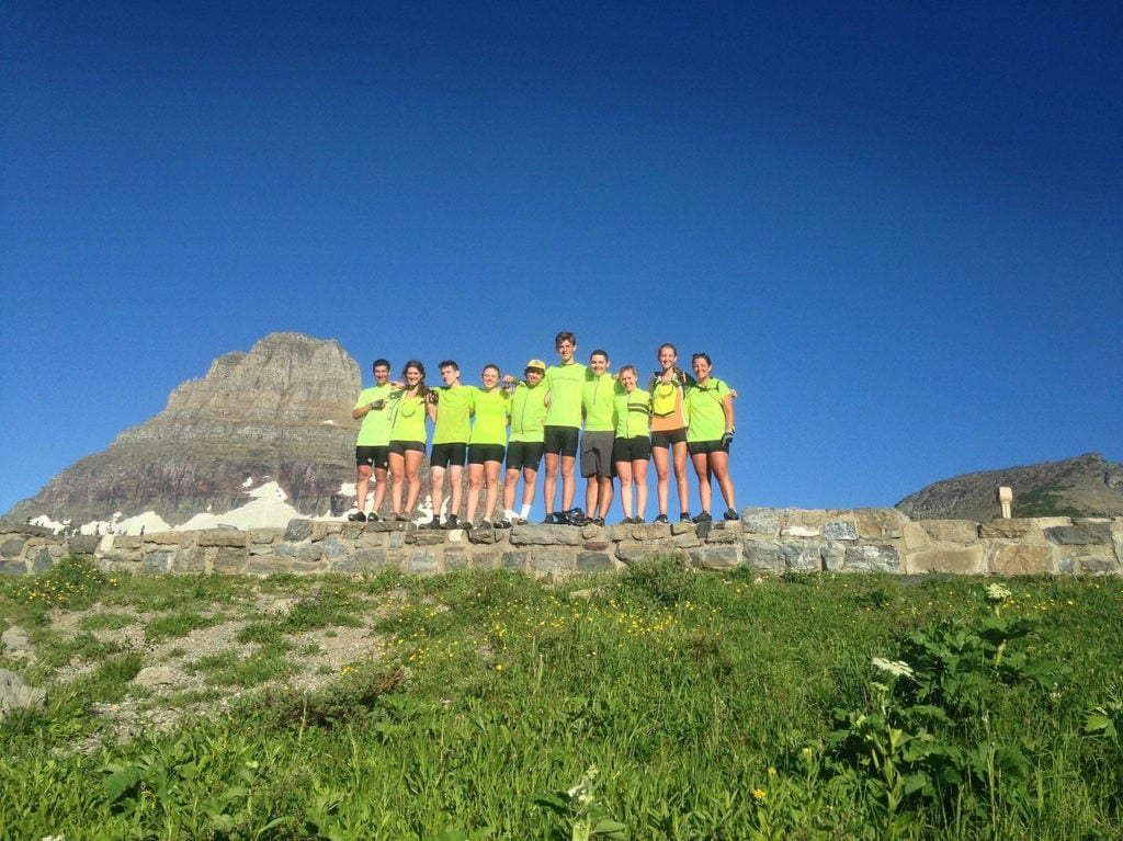 Teens pose on a stone ledge with a mountain in the background wearing bright colors after biking