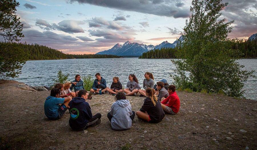 A group sharing dessert in the Tetons during their summer hiking trip.