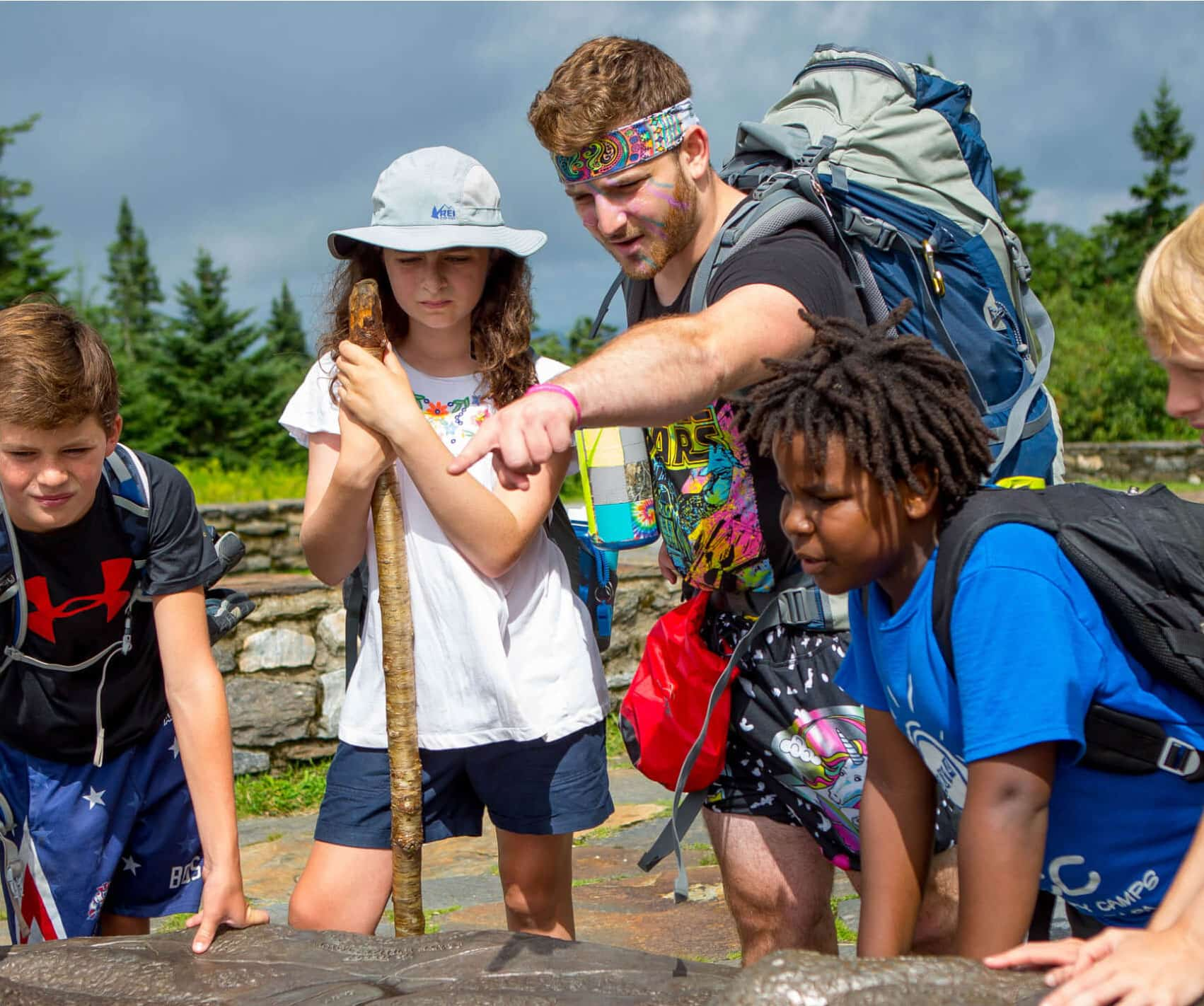 Leader points out hike to campers on a summer adventure program