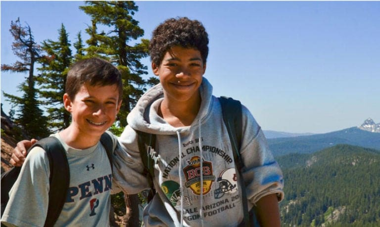 Friends take a photo while smiling above a scenic vista on a warm Summer day while hiking