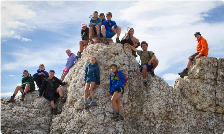 Teen hiking group gathers around a mountain on a teen summer adventure