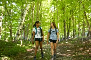 Teens hike in the woods while on their summer adventure trip