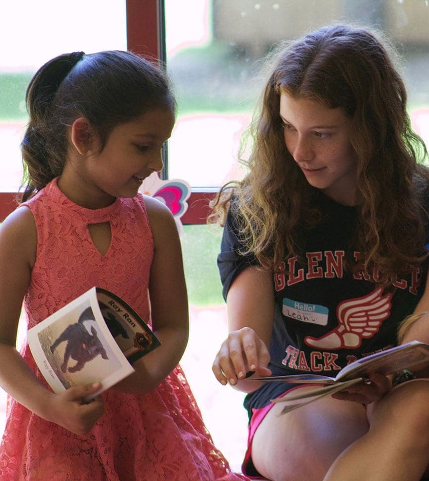 Teens interact with elementary students during a reading program while on their summer adventure program