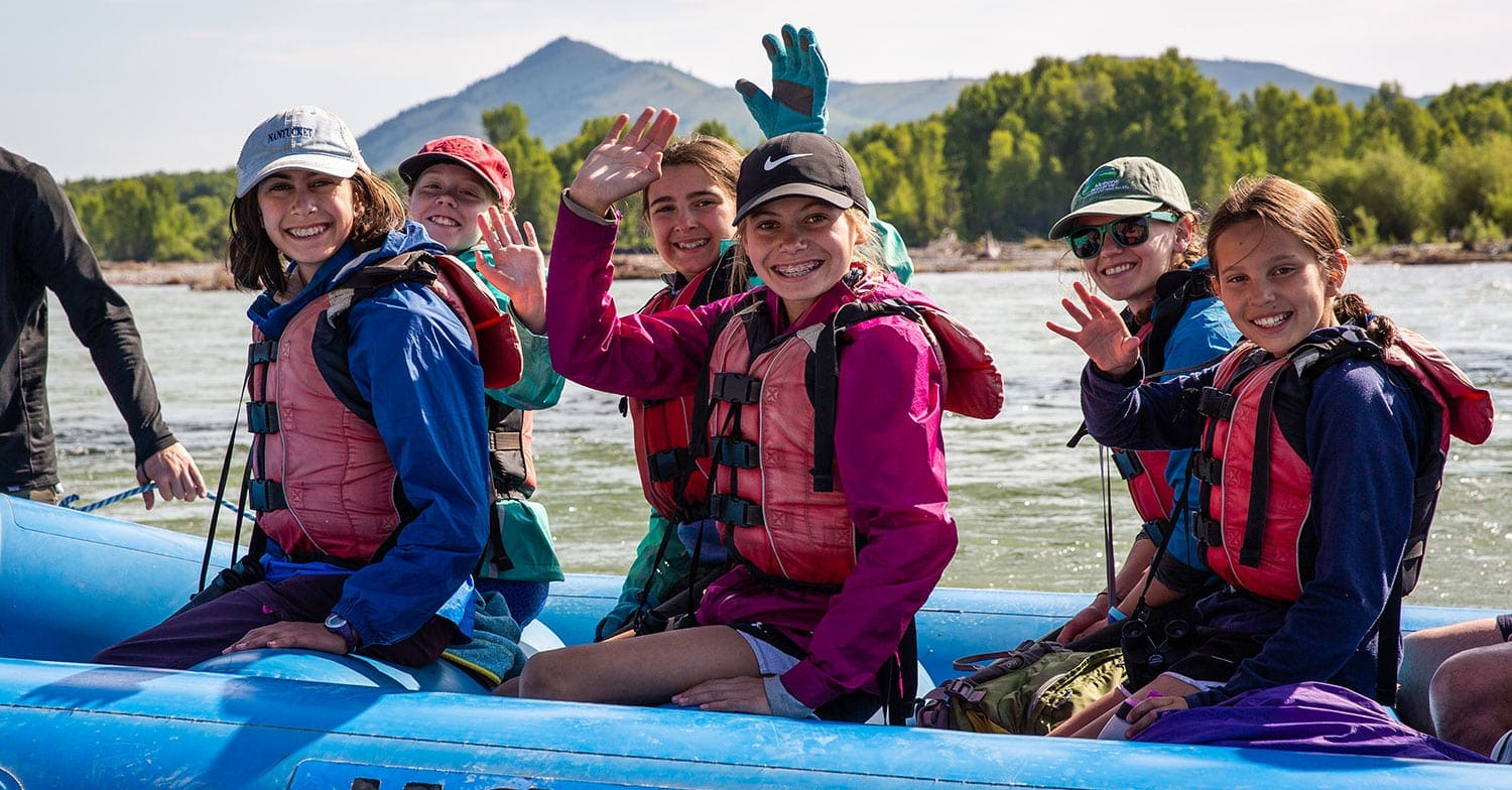 Campers wave while having blast on a rafting adventure trip with Overland Summers