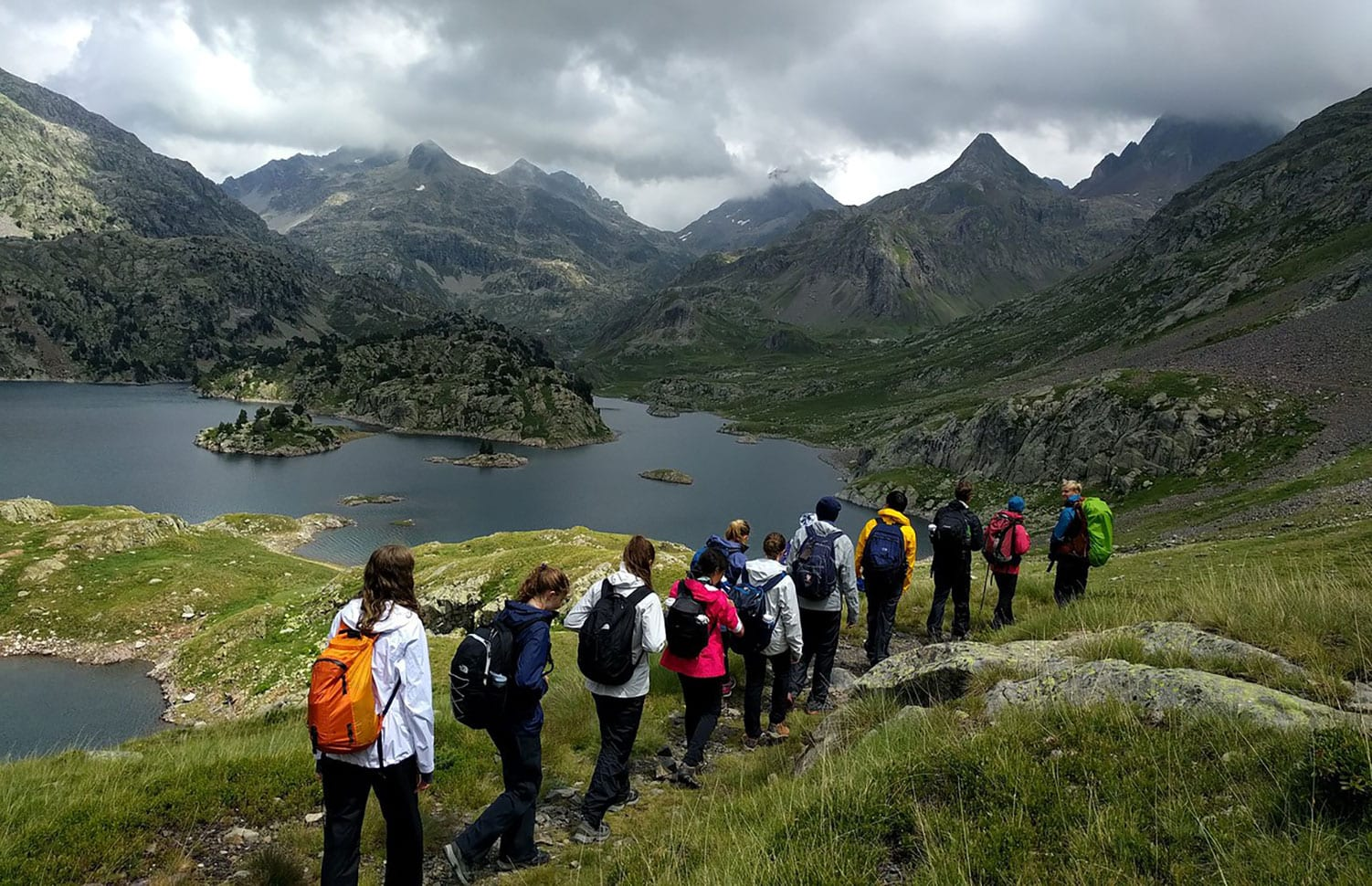 Teens hike single file into a beautiful summery mountain valley