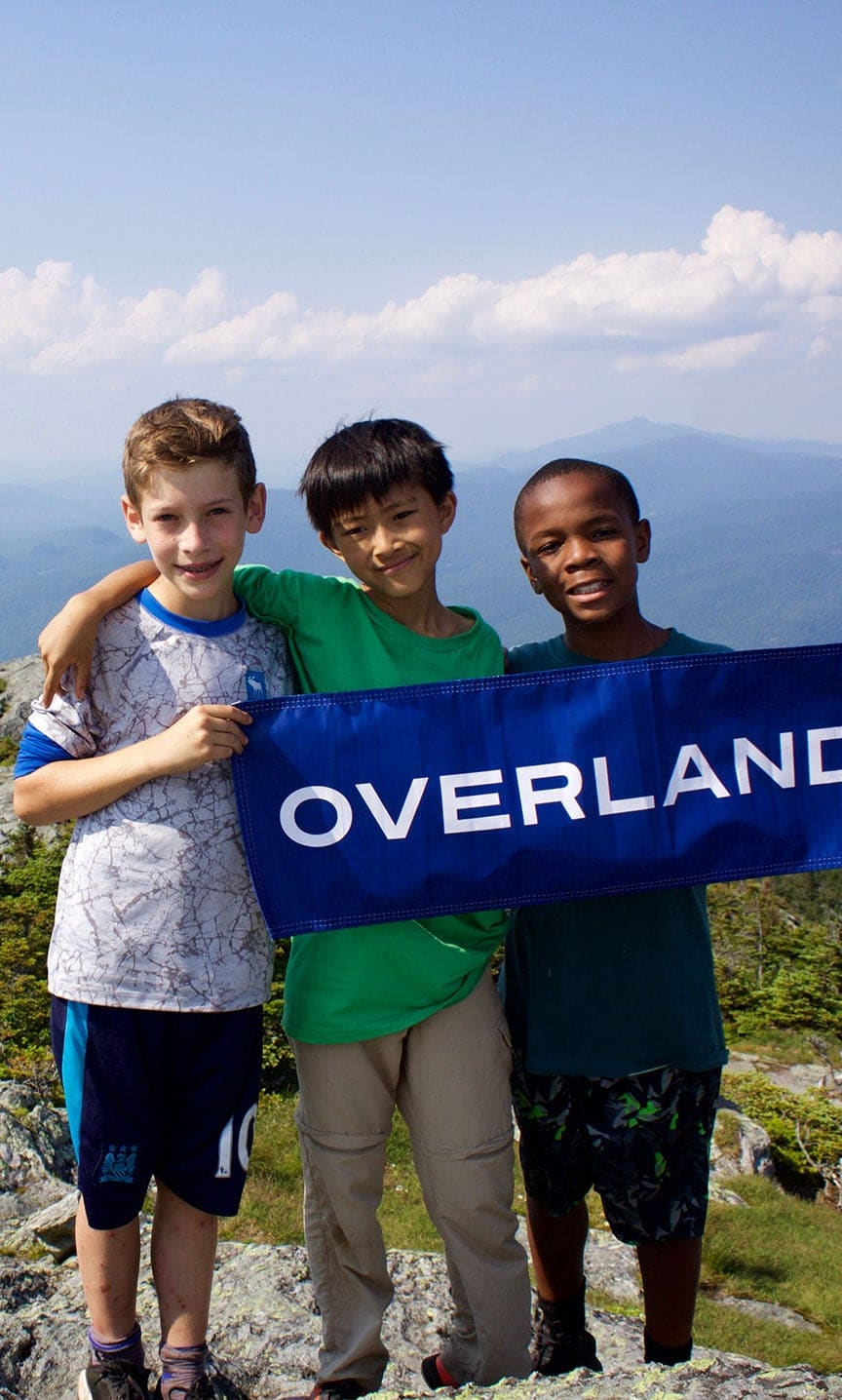 Campers hold up the Overland banner while on a summer adventure hiking trip