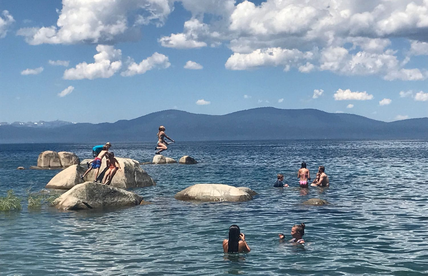 Campers enjoy a swim to cool off while hiking with Overland on one of our many teen summer adventures