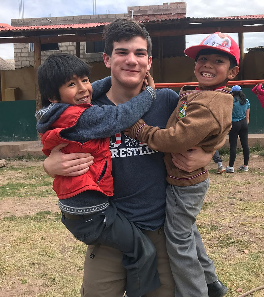 teen boy field studies with local children