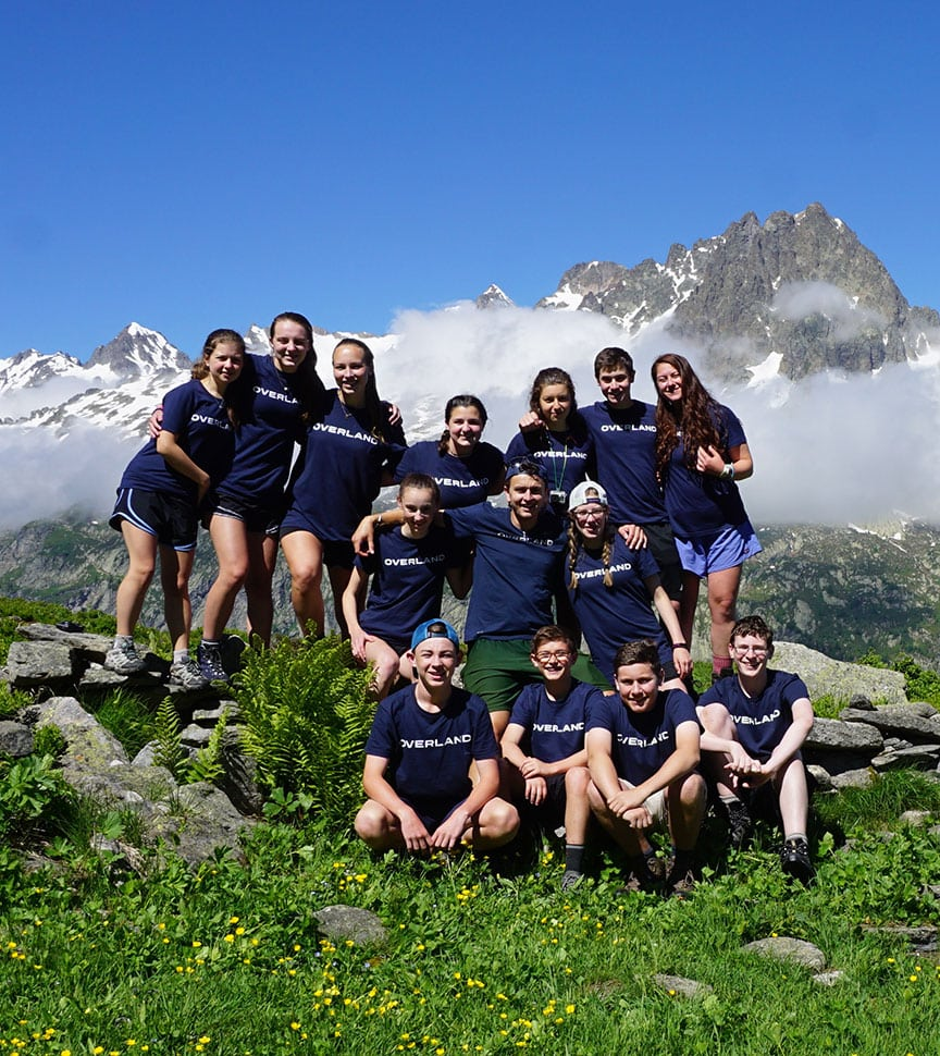 Teen campers gather for a group photo on a mountain summit while hiking on an overland summer adventure