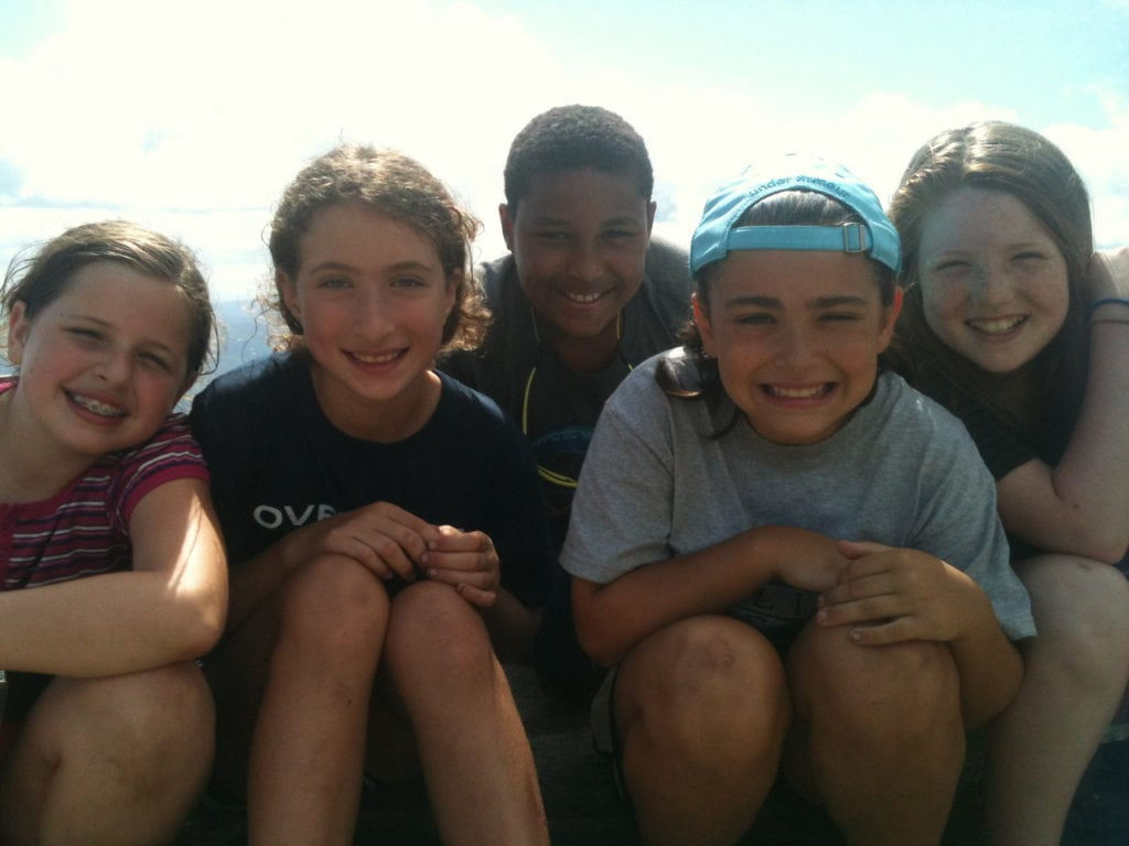 A group of students smiling outdoors, including Abbey on her first summer trip