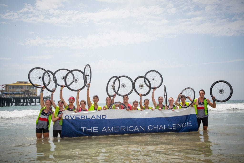 Abby and her American Challenge Group in the ocean holding their bike wheels to celebrate biking across the country