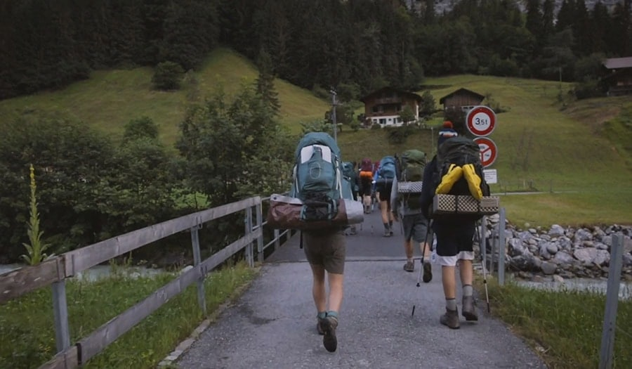 Teens hiking with big backpacks in the Alps during a challenging hiking trip
