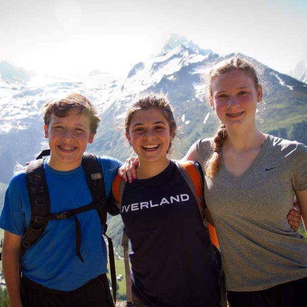 Teen campers smile while hiking in Europe on an summer adventure program with Overland