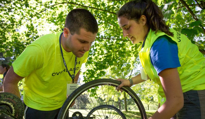 Leader learns how to change a flat tire while preparing for his summer biking trip