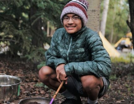Teen flashes a smile while camping out this Summer during an Overland hiking adventure