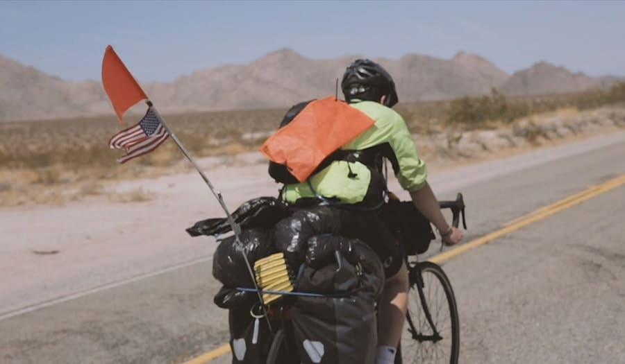 Teen biking through the desert in a helmet and high visibility clothes with mountains in the background