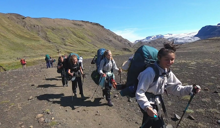 A group of teens wearing hiking backpacks and trekking poles smile while hiking in Iceland