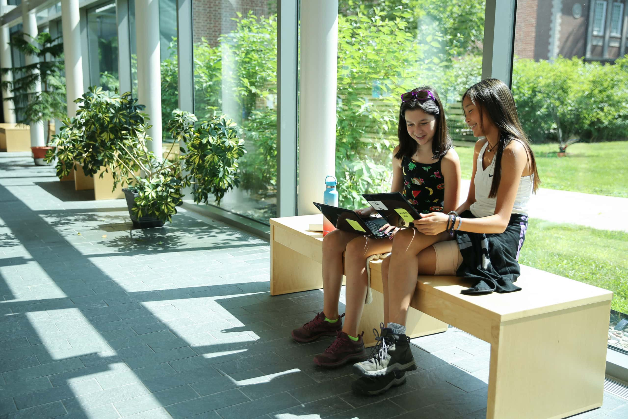 Two girls writing together and discussing their work during their writing program this summer