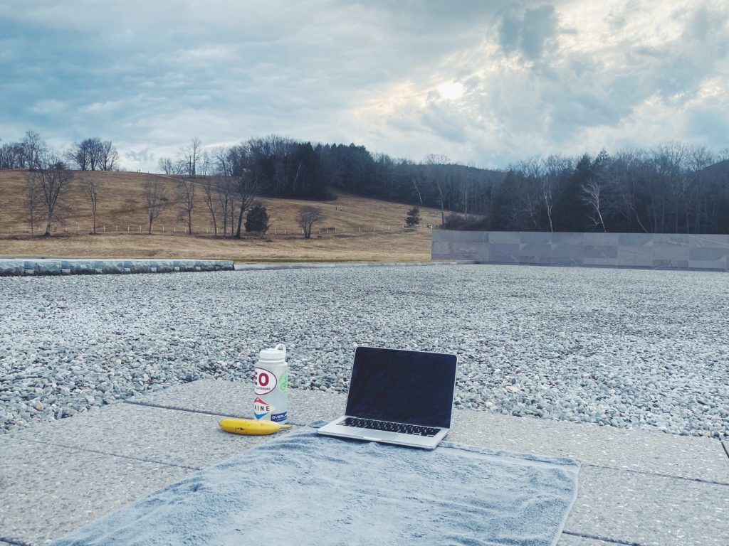 A yoga mat, laptop, and water bottle sit on a stone patio surrounded by gravel. In the background are rolling hills and pine trees, and the sky is cloudy.