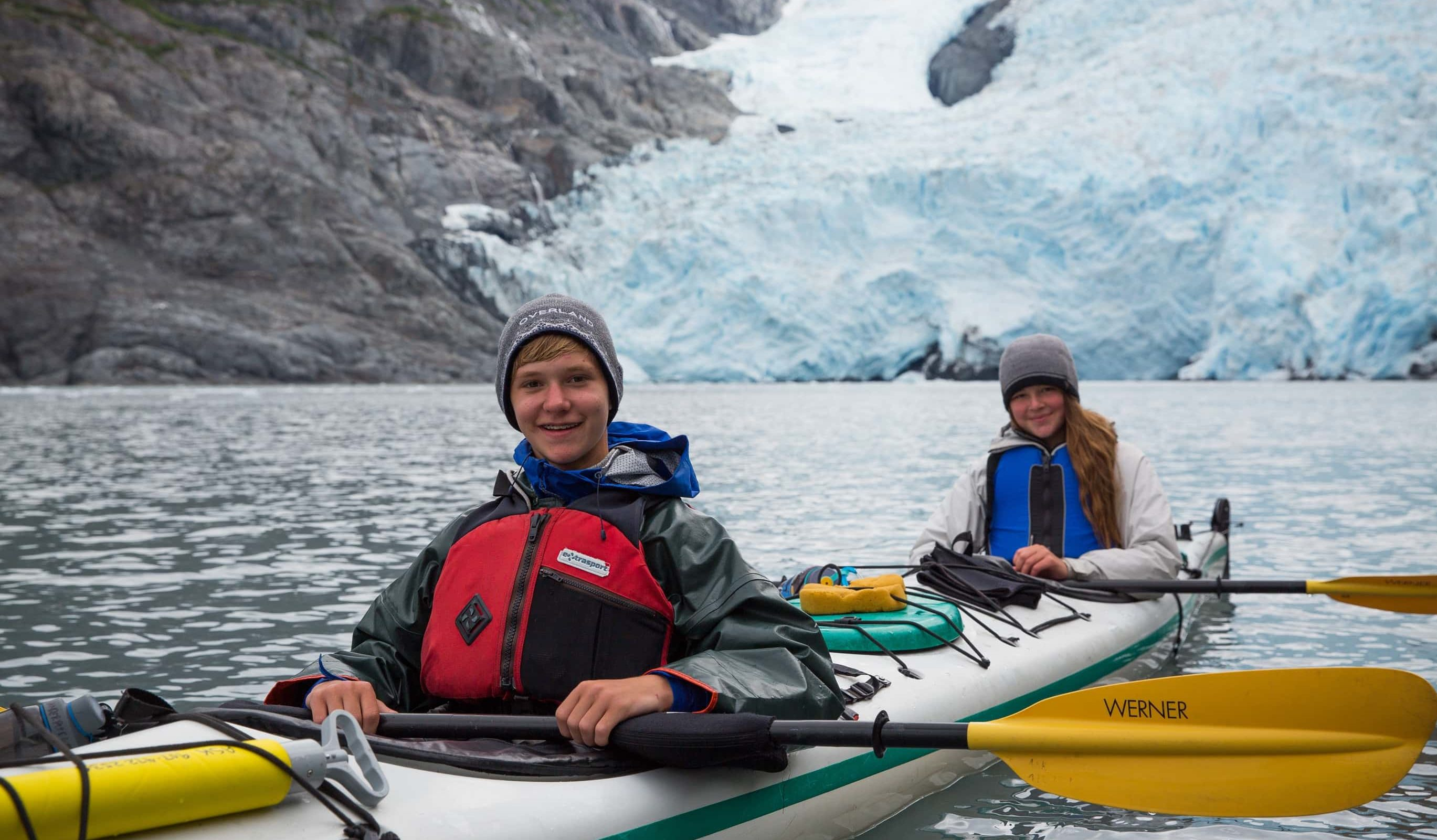 Boy smiling while sea kayaking in Alaska on a Teen Adventure Trip, with a glacier and another student in the background.
