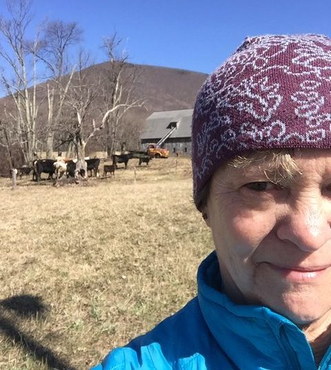 Closeup of a woman's face, wearing a warm hat, with a herd of cows grazing in the background